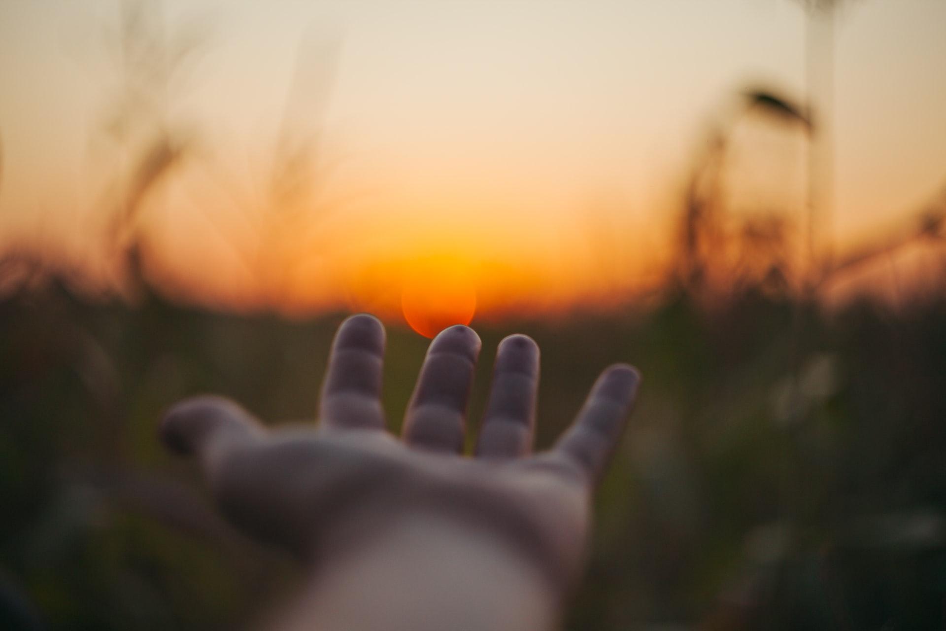 Mão estendida em fundo de paisagem, um convite para dar as mãos, confiar.
