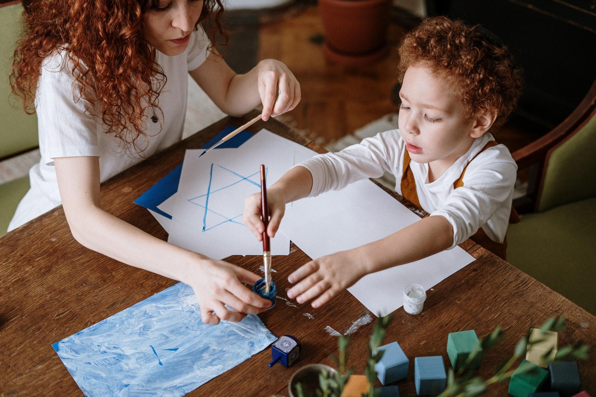 Mulher e criança desenhando uma estrela de David